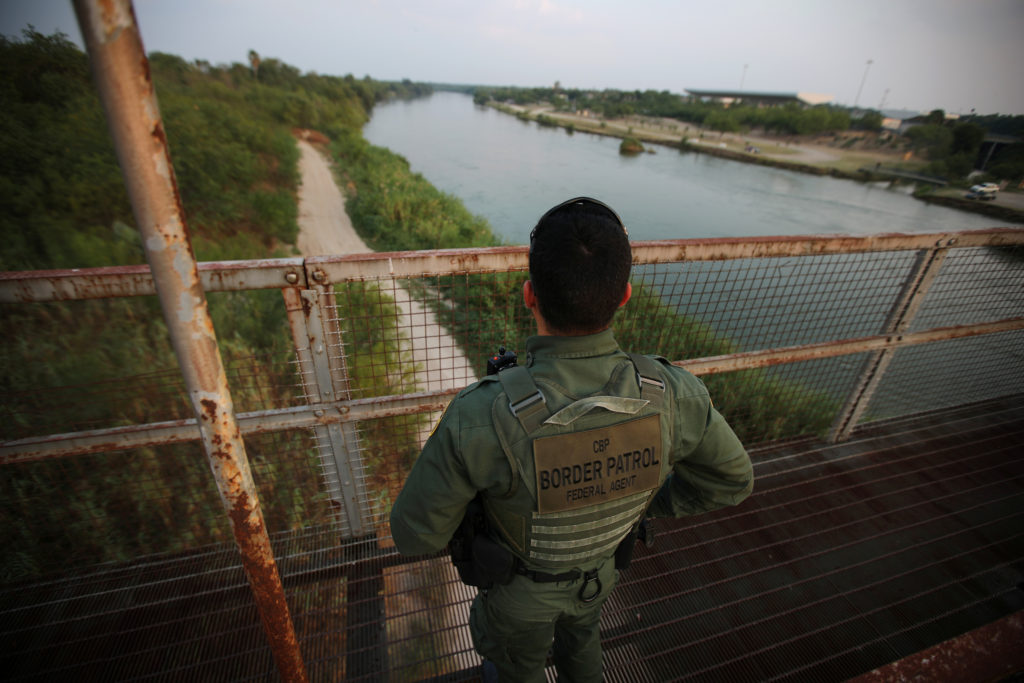A U.S. border patrol agent looks over the Rio Grande river at the border between United States and Mexico, in Roma, Texas, on May 11, 2017. In much of Texas, the river serves a a natural barrier for immigrants trying to cross the border. Photo by Carlos Barria/Reuters