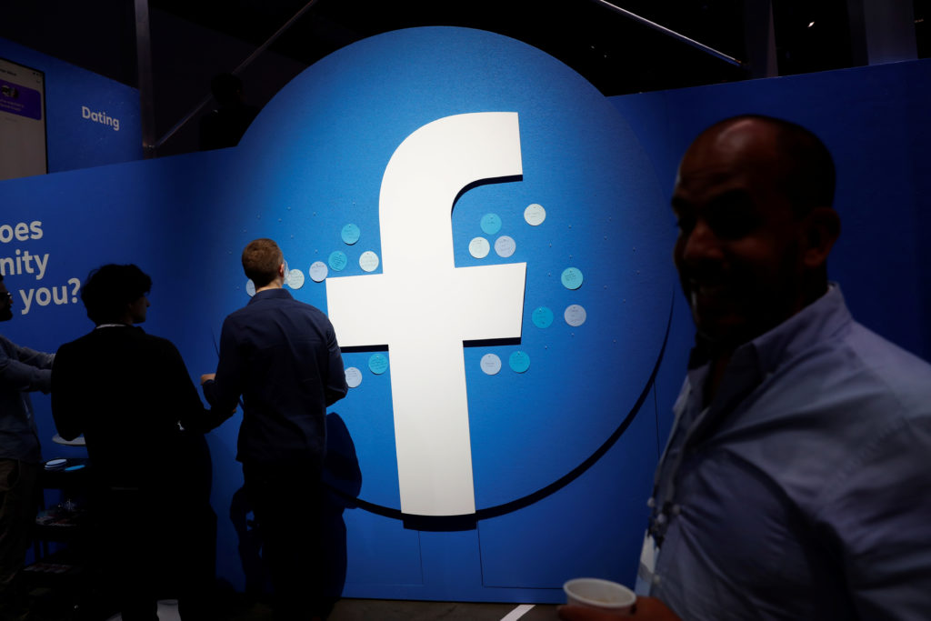 Attendees walk past a Facebook logo during Facebook Inc's F8 developers conference in San Jose, California, U.S., April 30, 2019. Photo by Stephen Lam/Reuters