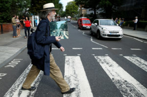 A man holds the iconic Beatles photo on Abbey Road as he recreates the photograph on the zebra crossing in London, Britain, in August. Henry Nicholls/Reuters