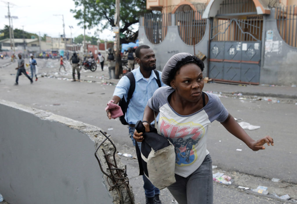 People run during a protest to demand the resignation of Haitian President Jovenel Moise, in Port-au-Prince, Haiti Septemb...