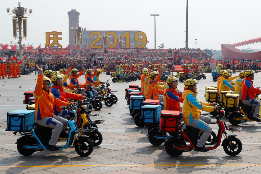Performers representing food delivery workers ride electric scooters during a parade marking the 70th founding anniversary of People's Republic of China, on its National Day in Beijing, China on October 1, 2019. Photo by Thomas Peter/Reuters