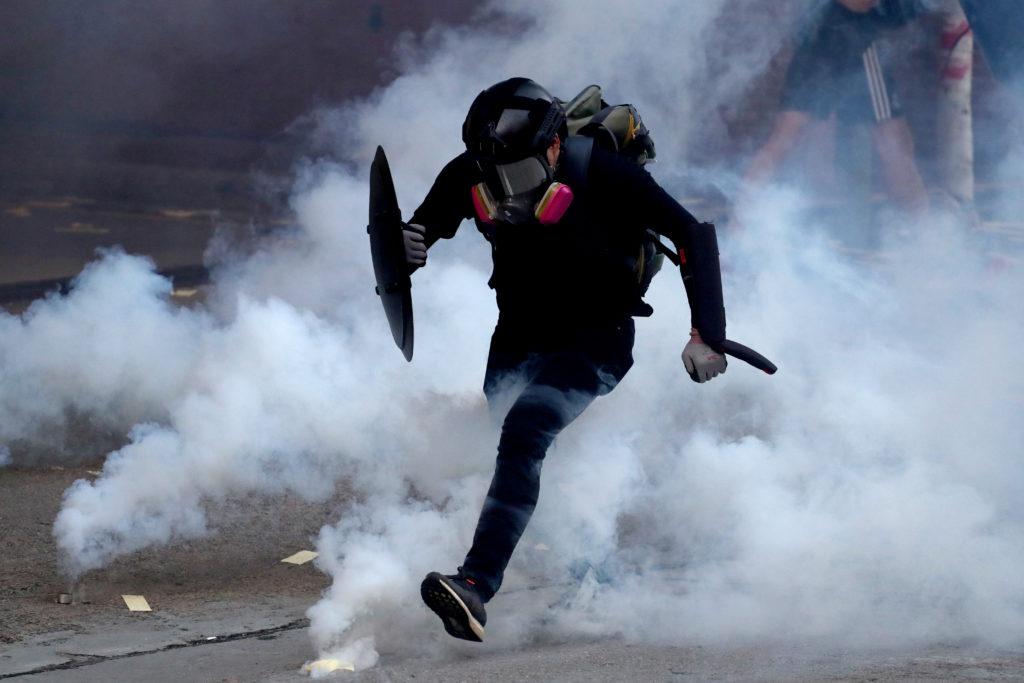 An anti-government protester runs through a cloud of tear gas durin…