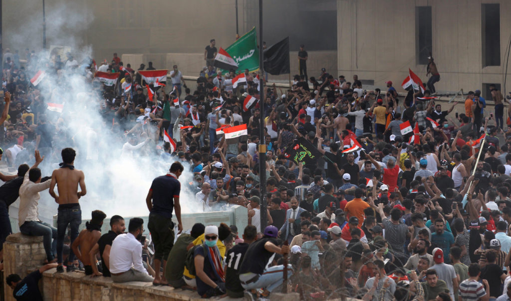 Demonstrators disperse as Iraqi Security forces use tear gas during a protest against government corruption amid dissatisf...
