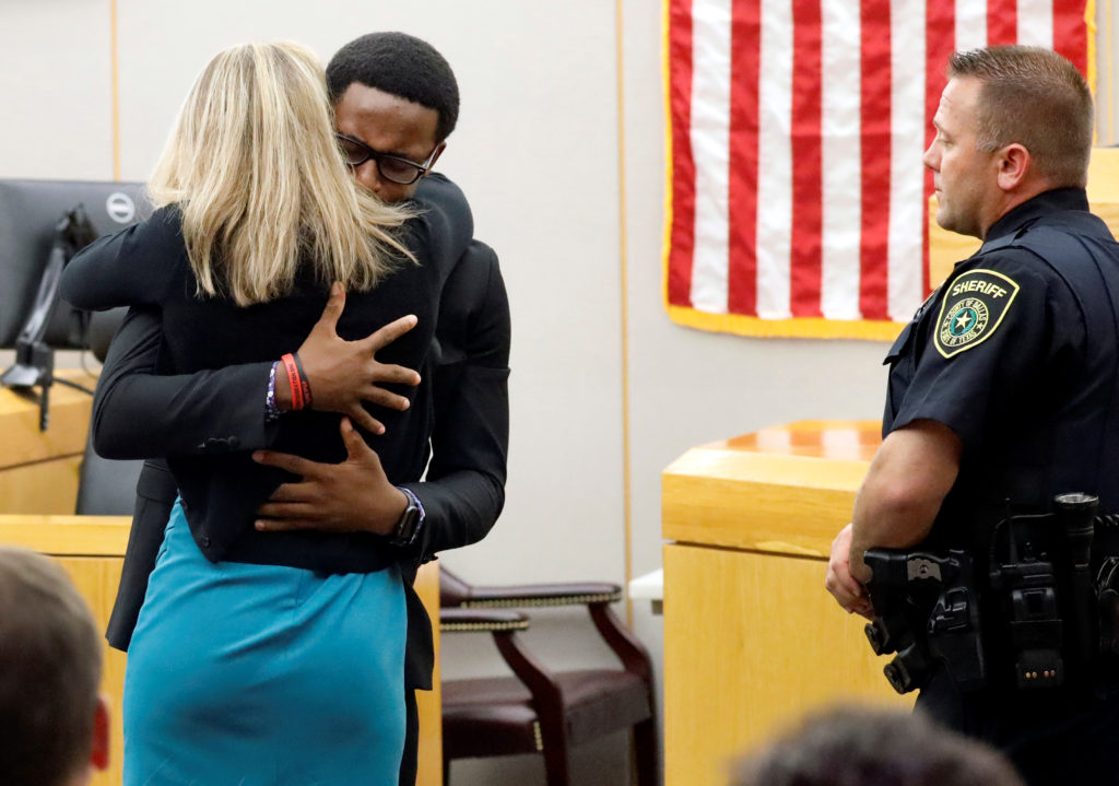Botham Jean's younger brother Brandt Jean hugs former Dallas police officer Amber Guyger after delivering his impact statement to her following her 10-year prison sentence for murder at the Frank Crowley Courts Building in Dallas, Texas, U.S. October 2, 2019. Photo by Tom Fox/Pool via Reuters