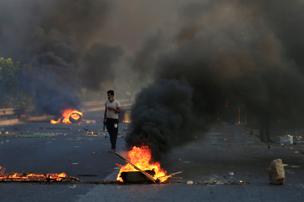 A man walks between burning tires and objects during a curfew, two …