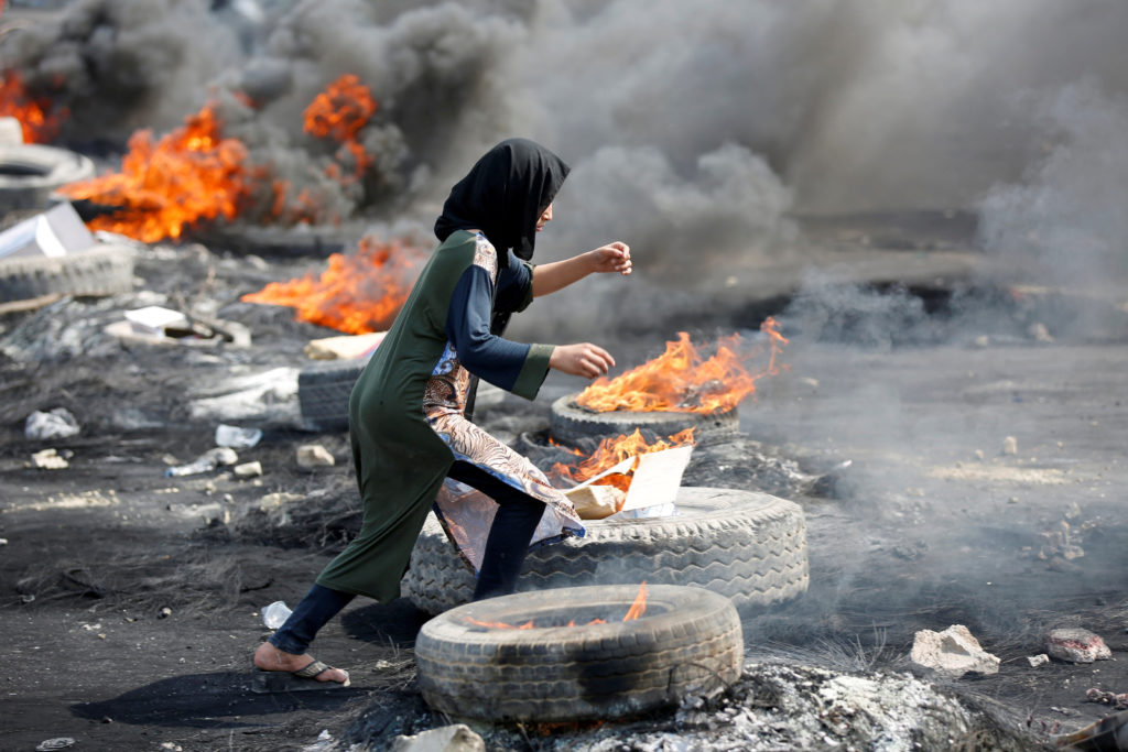 A demonstrator runs between burning tires during a curfew, two days…