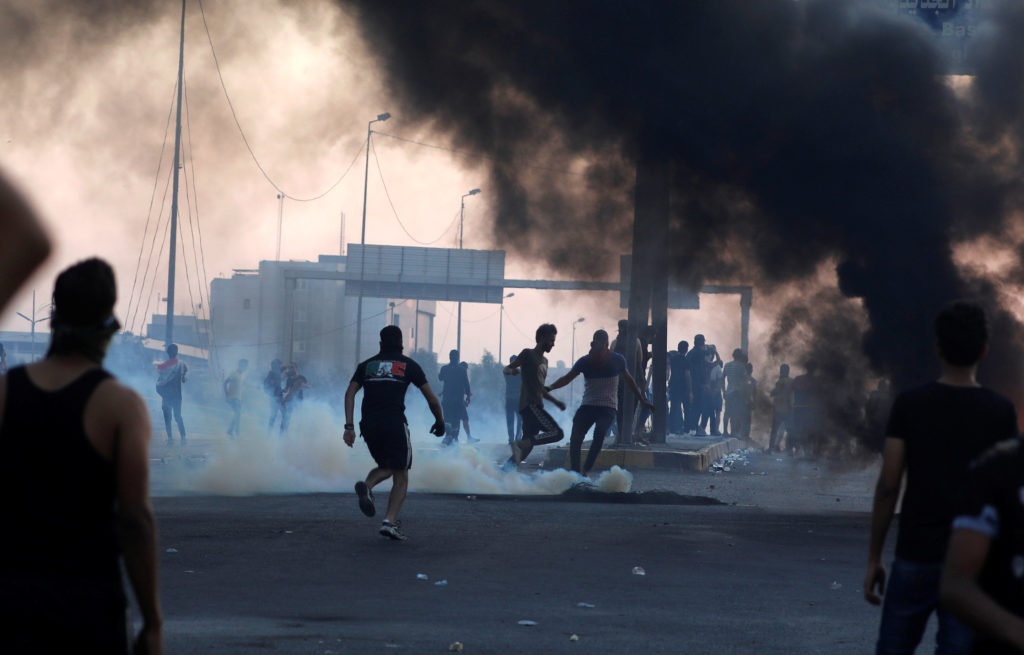 Demonstrators disperse as Iraqi security forces use tear gas during a protest after the lifting of the curfew, following f...