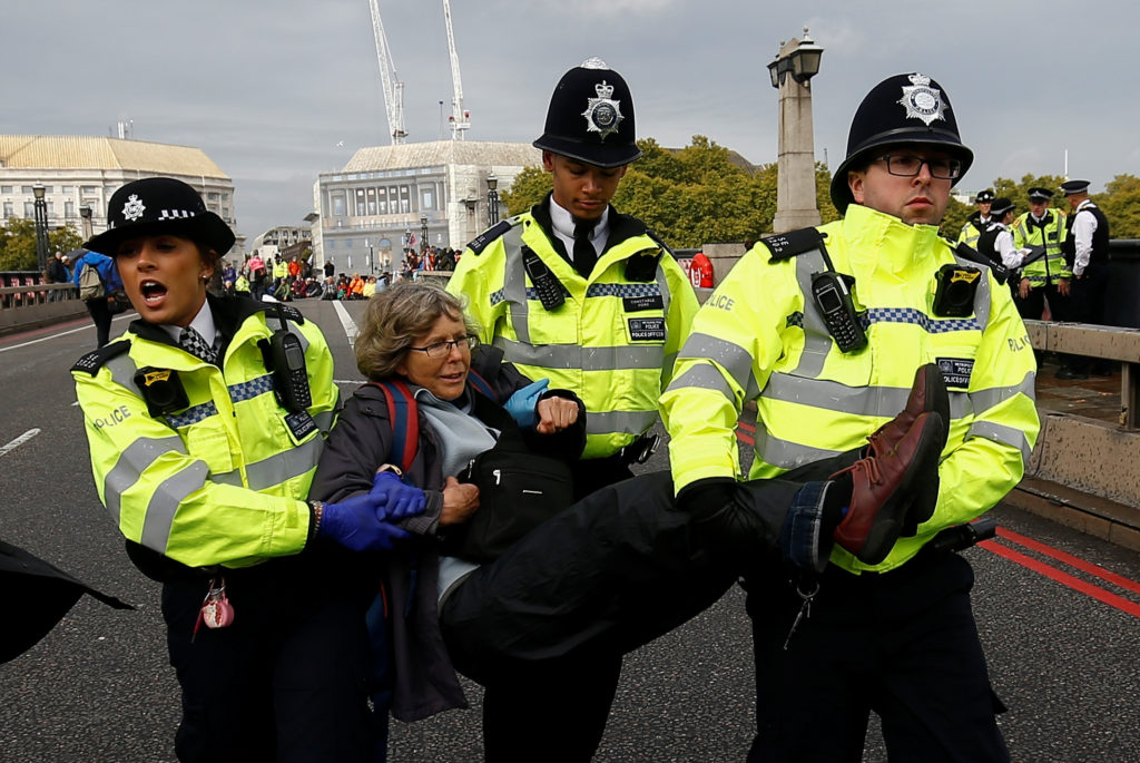 Police officers detain an activist at Lambeth Bridge during the Extinction Rebellion protest in London, Britain, October 7, 2019. Photo by Henry Nicholls/Reuters
