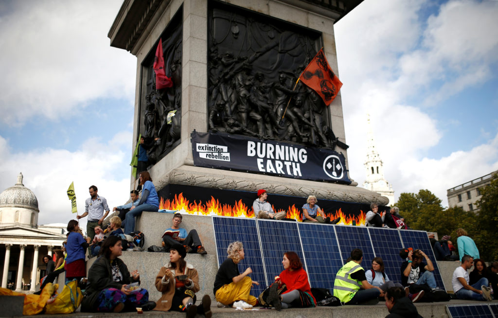 Extinction Rebellion protesters eat as they demonstrate at Trafalgar Square, in London, Britain, October 8, 2019. Photo by Henry Nicholls/Reuters