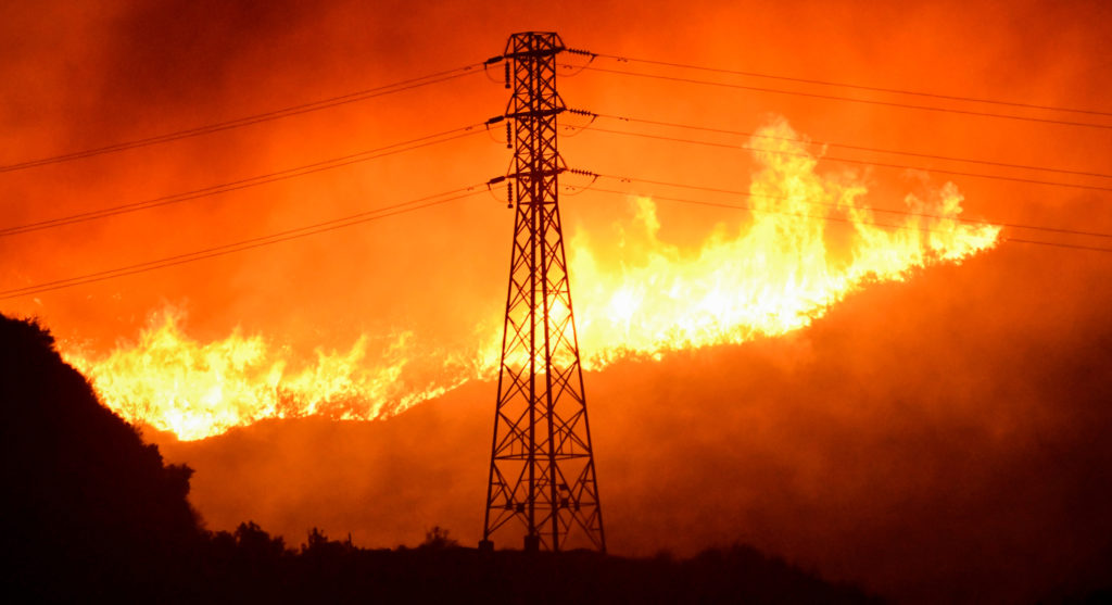 A wind-driven wildfire burns near power line tower in Sylmar, California, U.S., October 10, 2019. Photo by Gene Blevins/Reuters