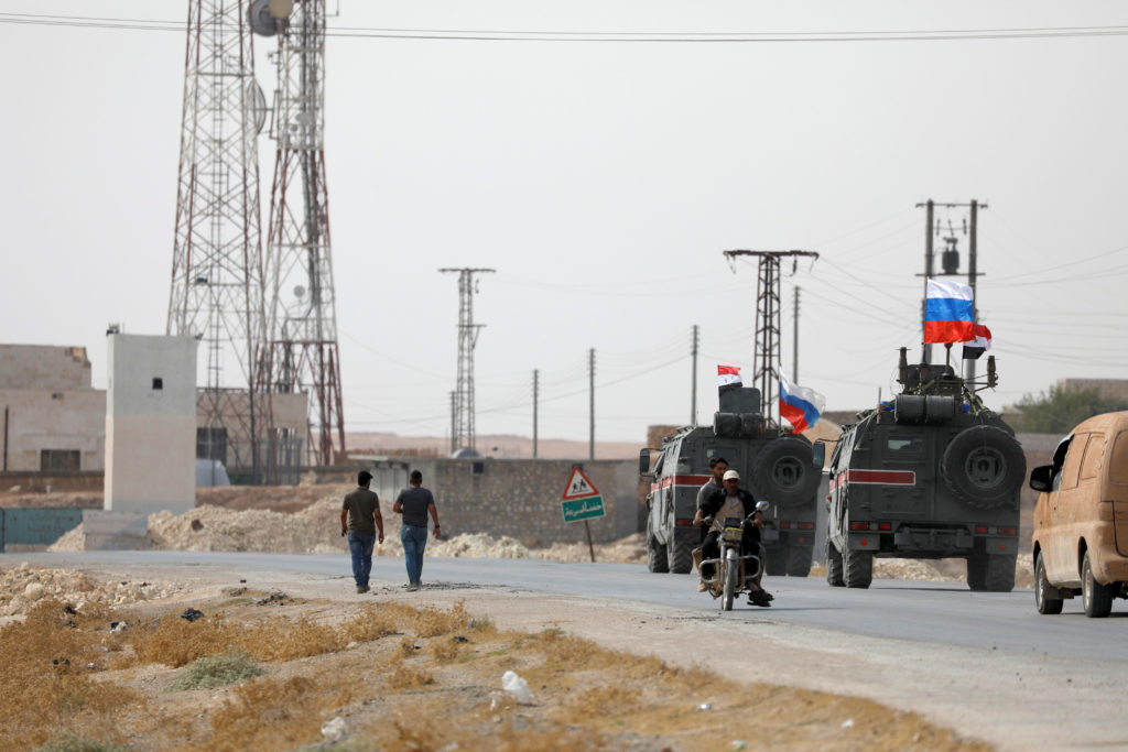 Russian and Syrian national flags flutter on military vehicles near Manbij, Syria October 15, 2019. Photo by Omar Sanadiki...