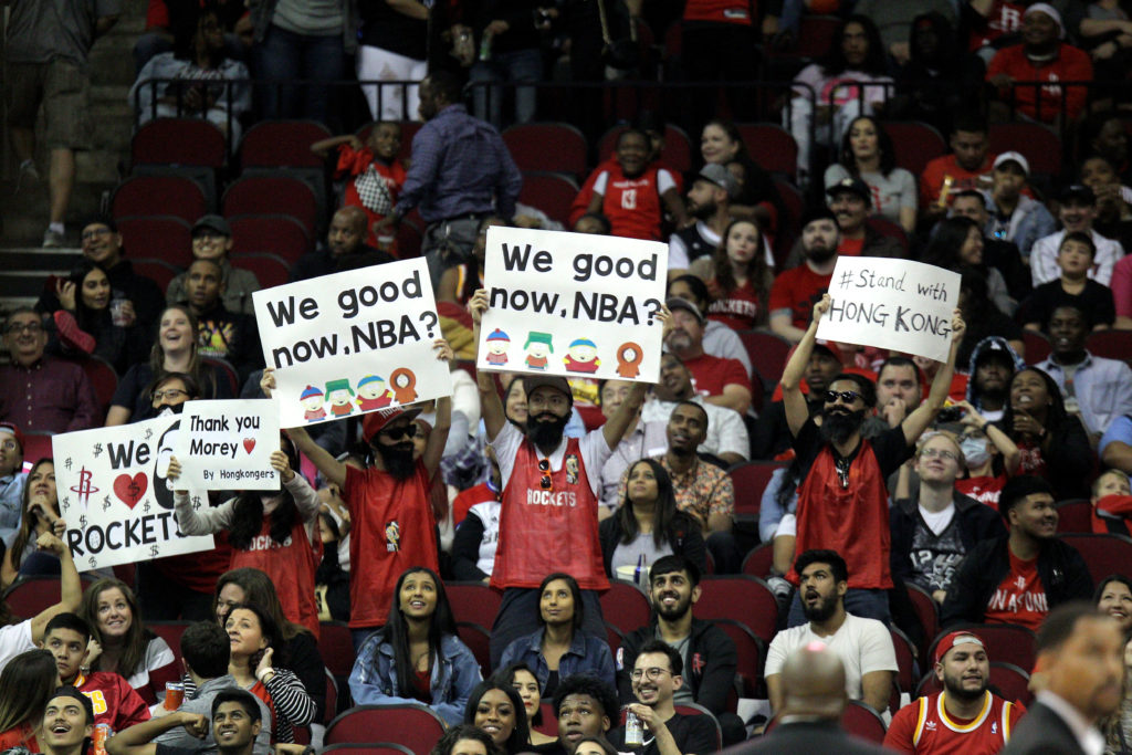 A group of Houston Rockets fans hold up signs in support of Houston…