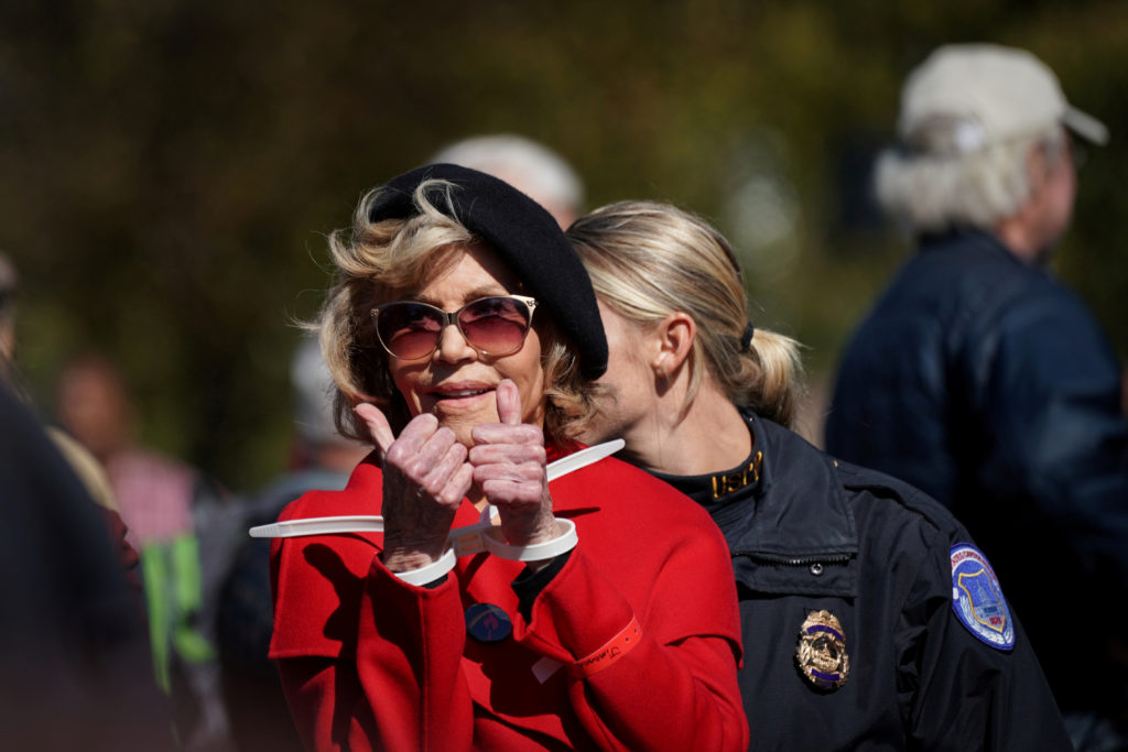 "Actor and activist Jane Fonda gives a thumbs up in handcuffs as she is detained for blocking the street in front of the Library of Congress during the ""Fire Drill Fridays"" protest in Washington, U.S., October 18, 2019. Photo by Sarah Silbiger/Reuters"
