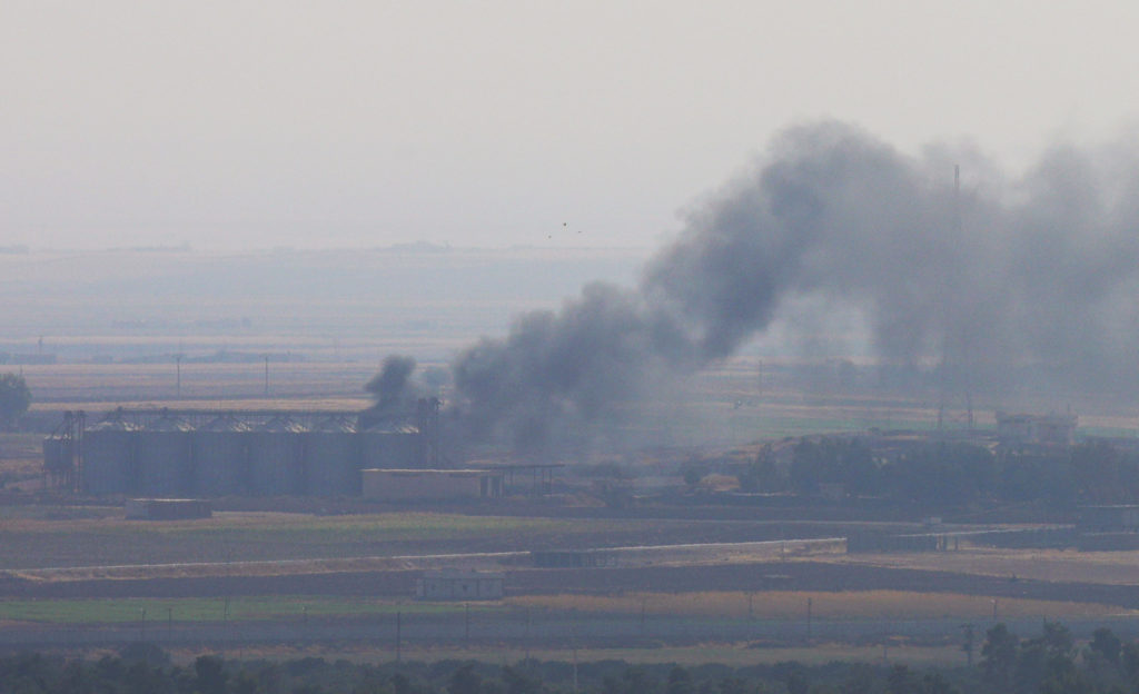 Smoke rises from a building near the Syrian town of Ras al-Ain as s…
