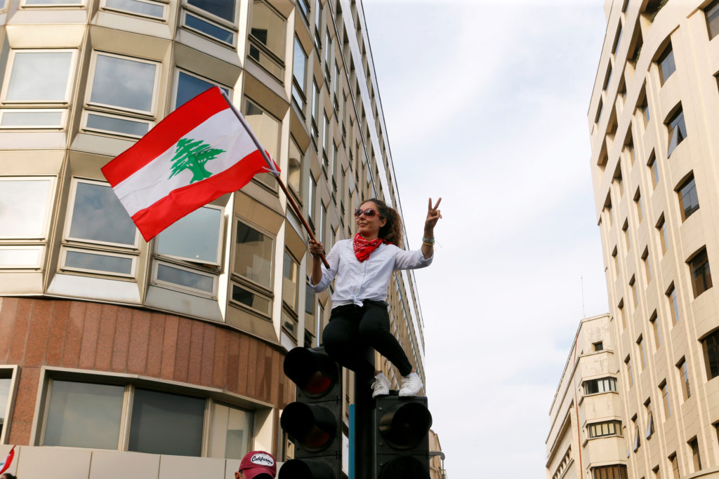 A demonstrator gestures as she holds a Lebanese flag during a protest over deteriorating economic situation, in Beirut, Lebanon October 18, 2019. Photo by Mohamed Azakir/Reuters