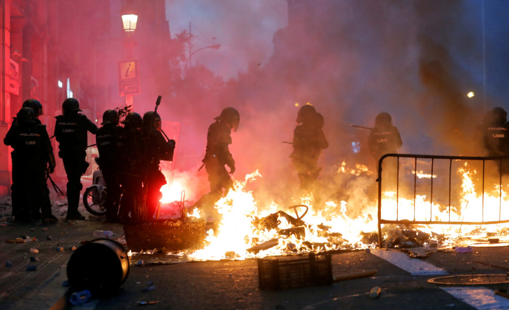 Riot police stand guard nexto to a burning barricade during Catalon…