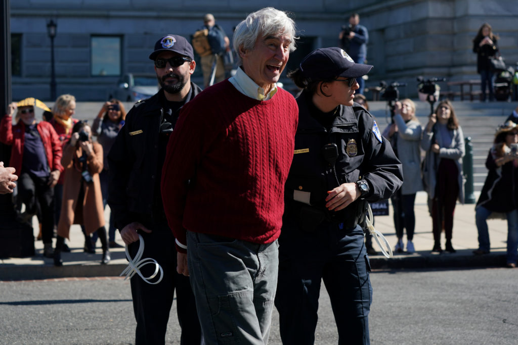 "Actor Sam Waterston is handcuffed and detained by Capitol Police during the ""Fire Drill Fridays"" protest outside the Library of Congress in Washington, U.S., October 18, 2019. Waterson's co-star in ""Grace & Frankie"", Jane Fonda, lead the demonstration and was also detained. Photo by Sarah Silbiger/Reuters"