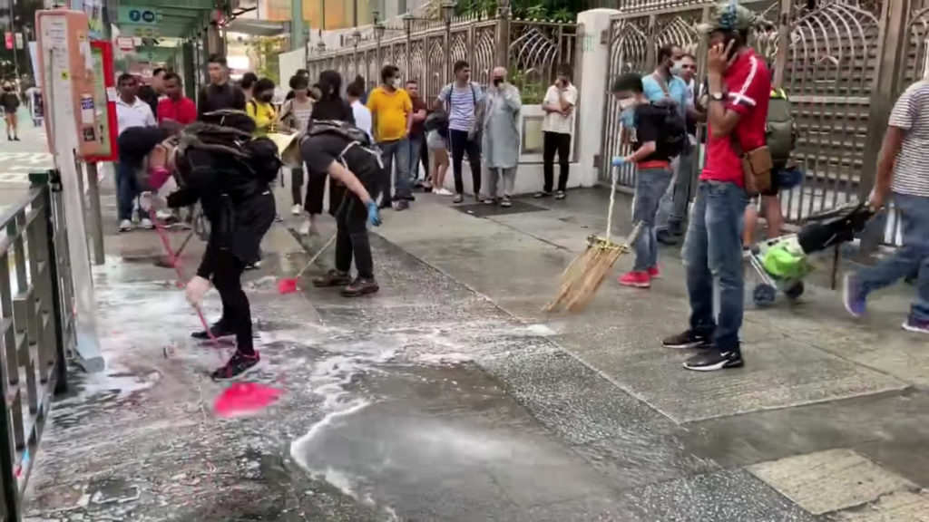People and protesters help cleaning up the blue dye that stained steps of the Kowloon Masjid and Islamic Centre in Hong Kong. Photo by Broadcast News Network/Hong Kong Baptist University via Reuters