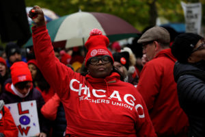 A woman clinches her fist as she waits for Democratic presidential candidate Senator Elizabeth Warren to visit a picket line of striking teachers in Chicago, U.S October 22, 2019. Photo by Joshua Lott/Reuters