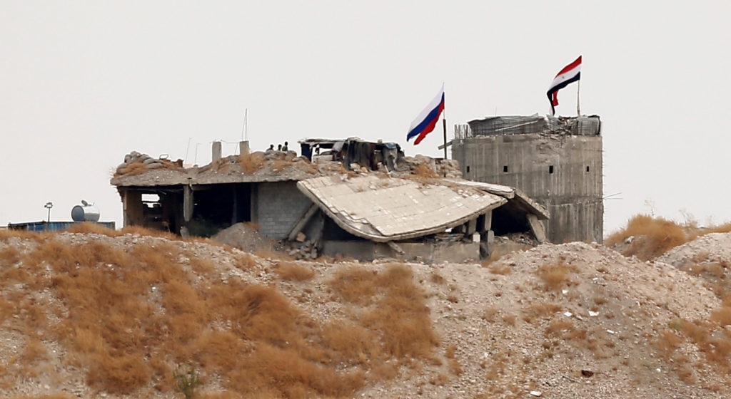 Russian and Syrian national flags are pictured near the northern Sy…