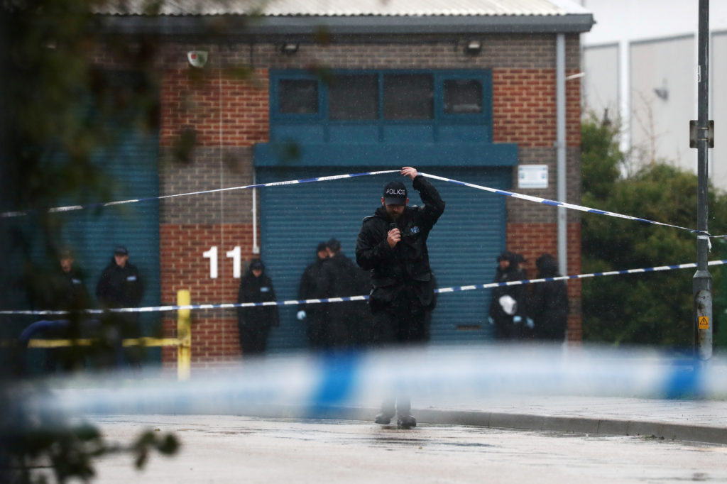 A police officer moves the tape inside the cordon, at the scene whe…