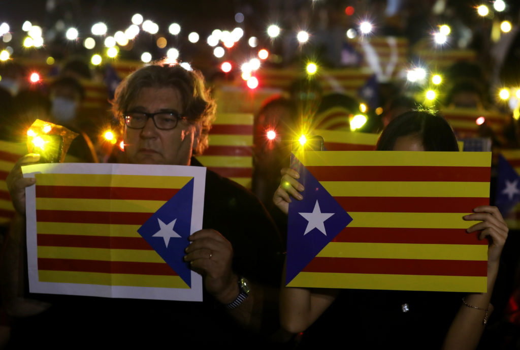 Pro-democracy demonstrators hold Esteladas (Catalan separatist flag) and flashlights during a protest in Hong Kong's Chate...