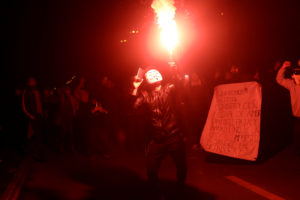 A demonstrator holds a flare during a protest against Chile's state economic model in Concepcion, Chile October 28, 2019. The banner reads 'We want our constitution made from mud and straw'. Photo by Juan Gonzalez/Reuters