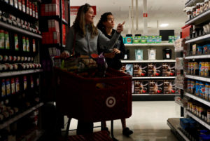 Solveig Woo (L) and daughter Katherine shop for supplies inside a darkened Target store during Pacific Gas & Electric's Public Safety Power Shutoff (PSPS) in Novato, California, U.S. October 29, 2019. Photo by Stephen Lam/Reuters