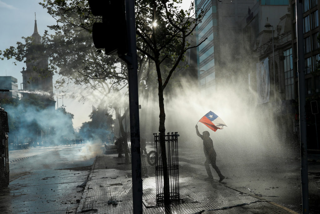 A demonstrator waves a Chilean flag as a riot police vehicle uses a water cannon during a protest against Chile's governme...