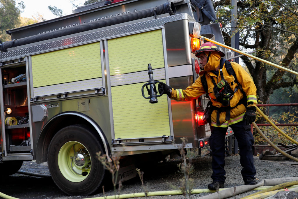 A firefighter passes a hose nozzle while working on a burning structure at the Kincade fire in Calistoga, California, U.S. October 29, 2019. Photo by Stephen Lam/Reuters