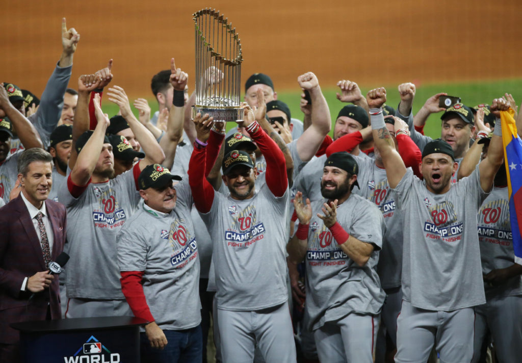 Washington Nationals manager Dave Martinez (4) and general manager Mike Rizzo hoist the Commissioners Trophy after defeating the Houston Astros in game seven of the 2019 World Series at Minute Maid Park. The Washington Nationals won the World Series winning four games to three. Oct 30, 2019; Houston, TX, USA; Mandatory Credit: Thomas B. Shea-USA TODAY Sports