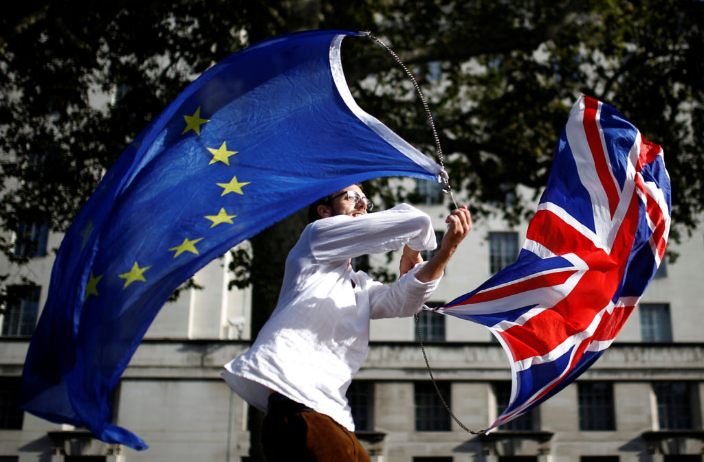 An EU supporter waves flags while other demonstrators march as parliament sits on a Saturday for the first time since the 1982 Falklands War, to discuss Brexit in London, Britain, October 19, 2019. Photo by Henry Nicholls/Reuters