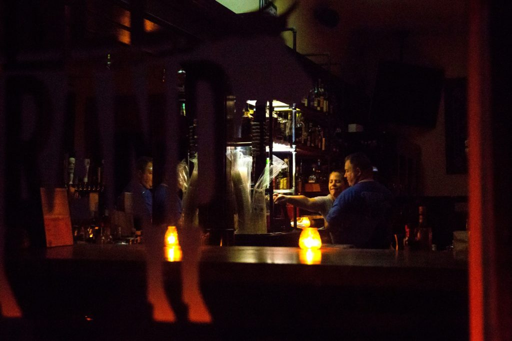 Restaurant owners Emily Schiffman and Kevin Dress use light from candles and a flashlight as they prepare to close up Reel and Brand in Sonoma, California, on October 9, 2019, after the Pacific Gas & Electric  utility company began planned power outages. Photo by Brittany Hosea-Small / AFP via Getty Images
