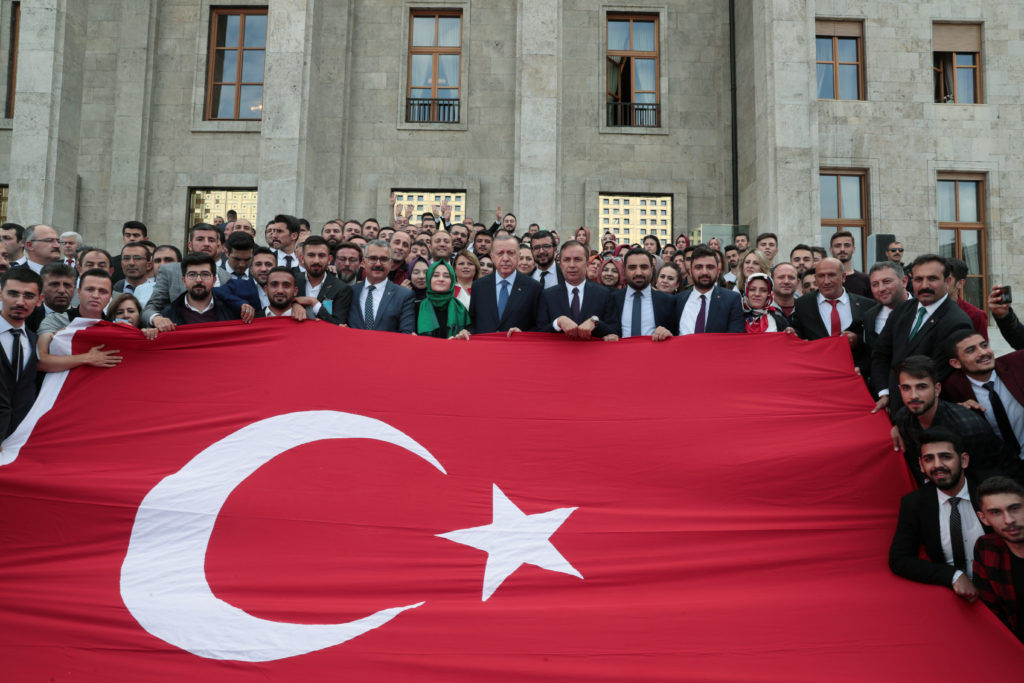 Turkish President Tayyip Erdogan poses with supporters of his ruling AK Party behind a national flag at the parliament in Ankara, Turkey, October 16, 2019. Photo by Murat Cetinmuhurdar / Presidential Press Office / Handout via REUTERS