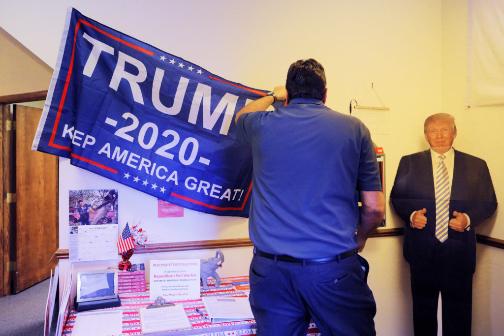 Keith Best, director of grassroots outreach, puts up a banner next to a cardboard cutout of U.S. President Donald Trump ahead of a leadership training session with local Republican Party officials and volunteers in Waukesha, Wisconsin, U.S., September 7, 2019. Picture taken September 7, 2019. Photo by REUTERS/Brian Snyder