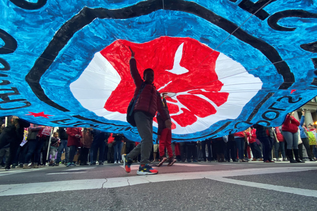 A child walks under a banner as hundreds of teachers and supporters march, days before the teacher's union was set to go o...