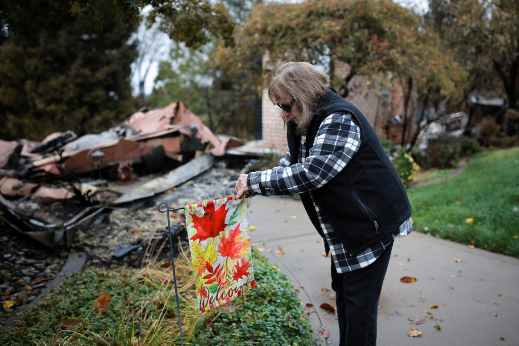 FILE PHOTO: Gerryann Wulbern rehangs a welcome sign she found unburned on her lawn after returning to her home for the fir...