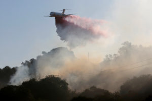 A plane drops fire retardant on the Maria Fire in the early morning in Santa Paula, California, U.S. November 1, 2019. Photo by Daniel Dreifuss/Reuters