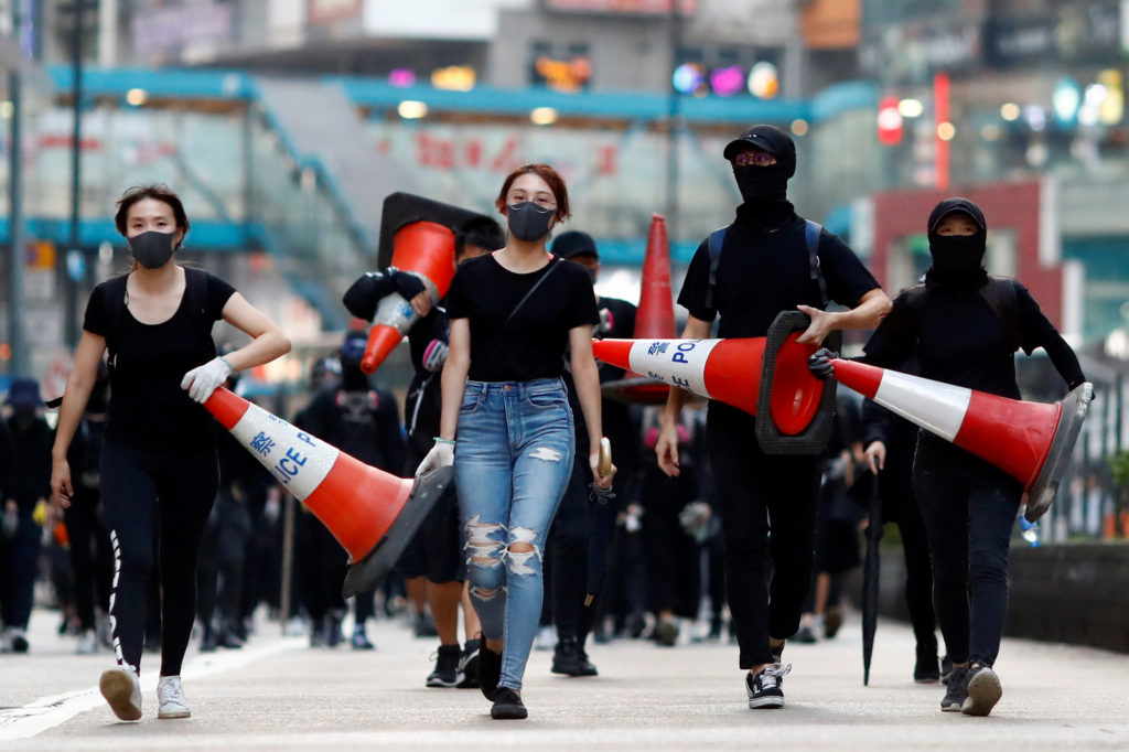 Protesters walk down the road with traffic cones to build a barricade in Causeway Bay, Hong Kong, China November 11, 2019. Photo by Thomas Peter/Reuters