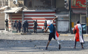A demonstrator throws objects toward members of Iraqi security forces are seen during the ongoing anti-government protests in Baghdad, Iraq November 11, 2019. REUTERS/Thaier al-Sudani