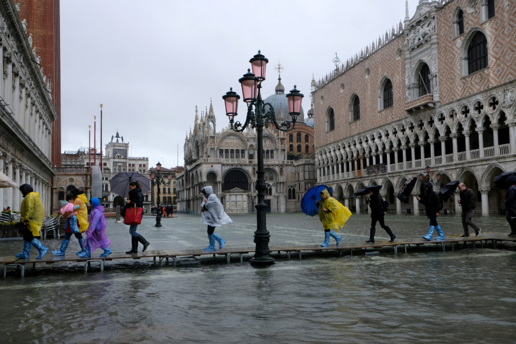 FILE PHOTO: People walk on a catwalk in the flooded St. Mark's Square in Venice, Italy November 12, 2019. Photo by Manuel Silvestri/Reuters/File Photo.
