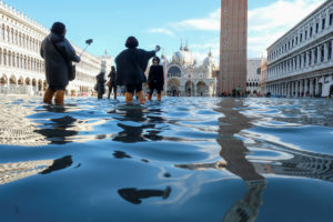 Tourists take pictures in the flooded St. Mark's Square during a period of seasonal high water in Venice, Italy, November 14, 2019. Photo by Manuel Silvestri/Reuters.