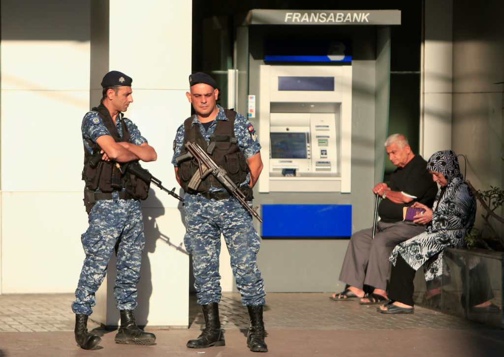 Lebanese police stand outside a Fransabank branch in Sidon, Lebanon on November 19, 2019. With widespread protests, some investors fear a bank run could collapse the country's banking system. Photo by Ali Hashisho/Reuters