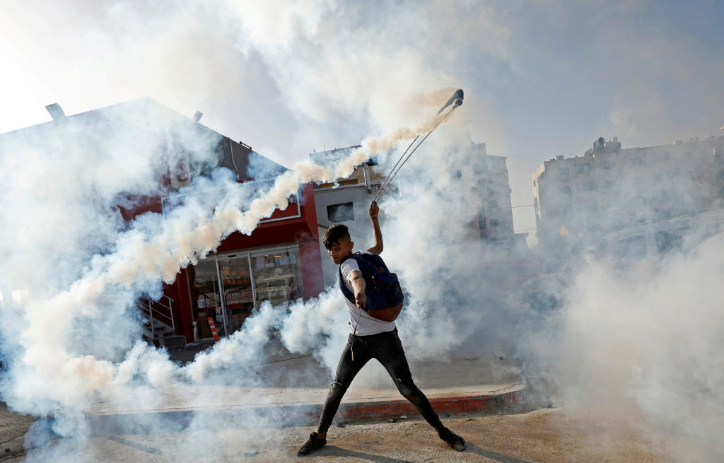 A demonstrator returns a tear gas canister during a protest as Palestinians call for a day of rage over U.S. decision on J...
