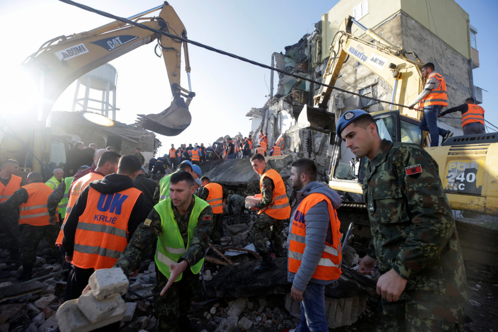 Emergency personnel work near a damaged building in Thumane, after an earthquake shook Albania, November 26, 2019. Photo b...