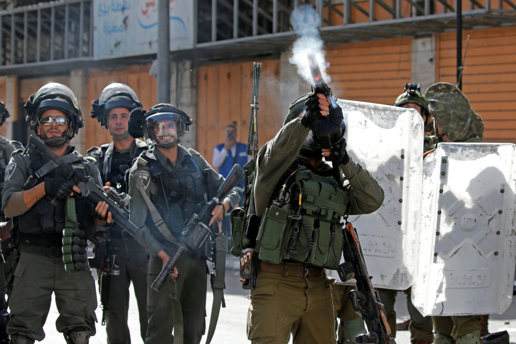 An Israeli soldier fires a weapon during a protest as Palestinians call for a day of rage over U.S. decision on Jewish settlements, in Hebron in the Israeli-occupied West Bank November 26, 2019. Photo by Mussa Qawasma/Reuters