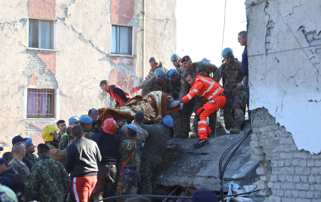 Military and emergency personnel carry an injured man on a stretcher near a damaged building in Thumane, after an earthquake shook Albania, November 26, 2019. Photo by Flatos Bytyci/Reuters