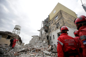 Emergency personnel stand on debris of collapsed and damaged buildings following Tuesday's powerful earthquake in Thumane, Albania, November 27, 2019. Photo by Florion Goga/Reuters