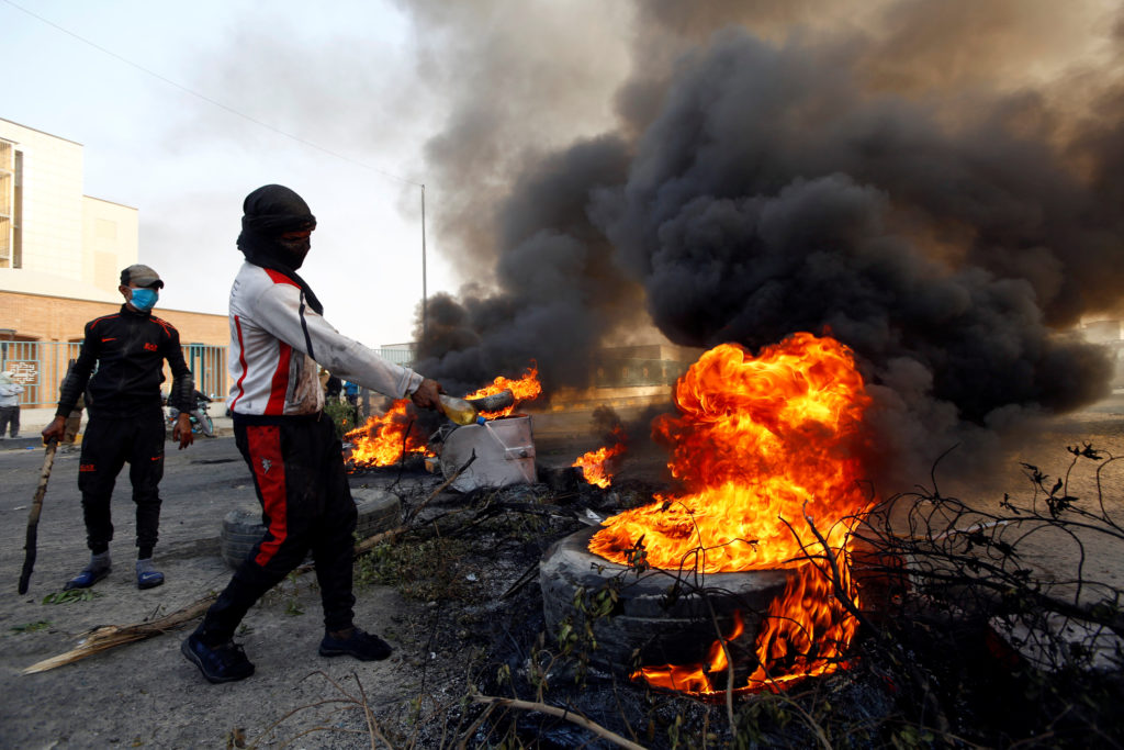 A protester pours fuel on a tire to burn it as he blocks a street during ongoing anti-government protests in Najaf, Iraq N...