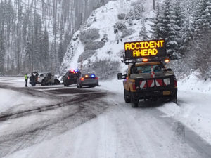 "A car with a sing reading ""Accident ahead"" stands near a scene where a rock fell on a highway and caused some vehicles damage in Santiam Pass, Oregon, U.S., November 26, 2019 in this picture obtained from social media. Picture taken November 26, 2019. OREGON DOT/via REUTERS"